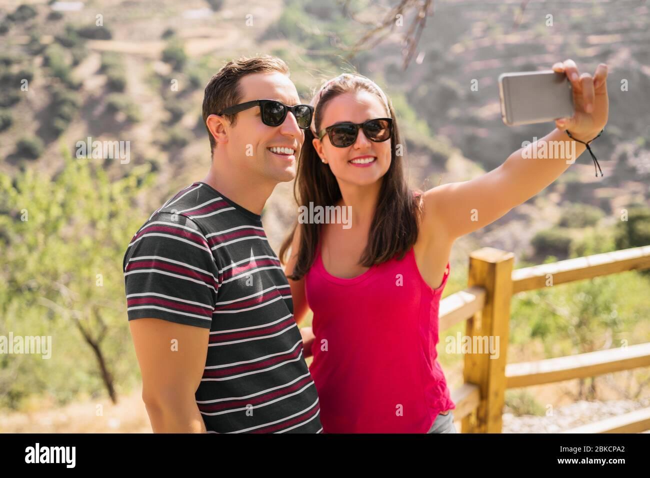 Coppia felice di viaggio facendo selfie montagne sfondo, colori estivi soleggiati, umore romantico. Occhiali da sole eleganti. Felici risate facce emotive. Foto Stock
