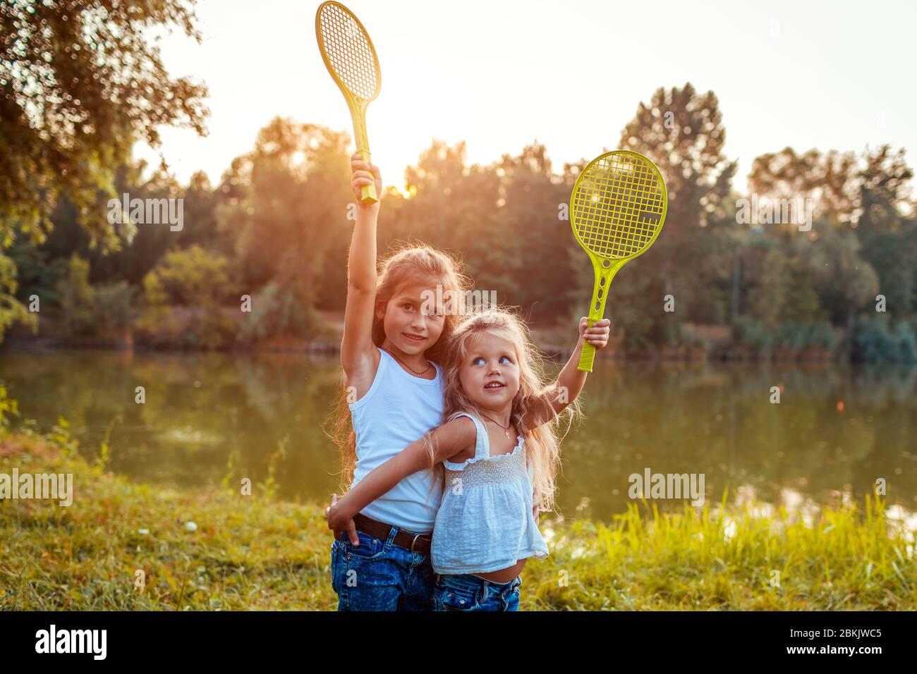 Ragazze che si divertono all'aperto dopo aver giocato badminton. Le sorelle sollevano le racchette nel parco primaverile. Attività per bambini Foto Stock