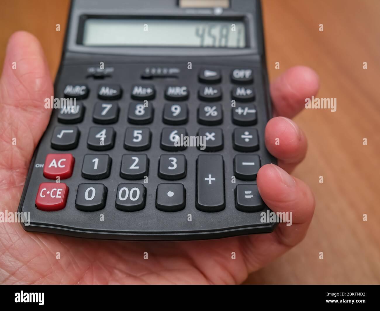 5 primo piano della mano umana con una calcolatrice nera con messa a fuoco selettiva e profondità di campo bassa Foto Stock