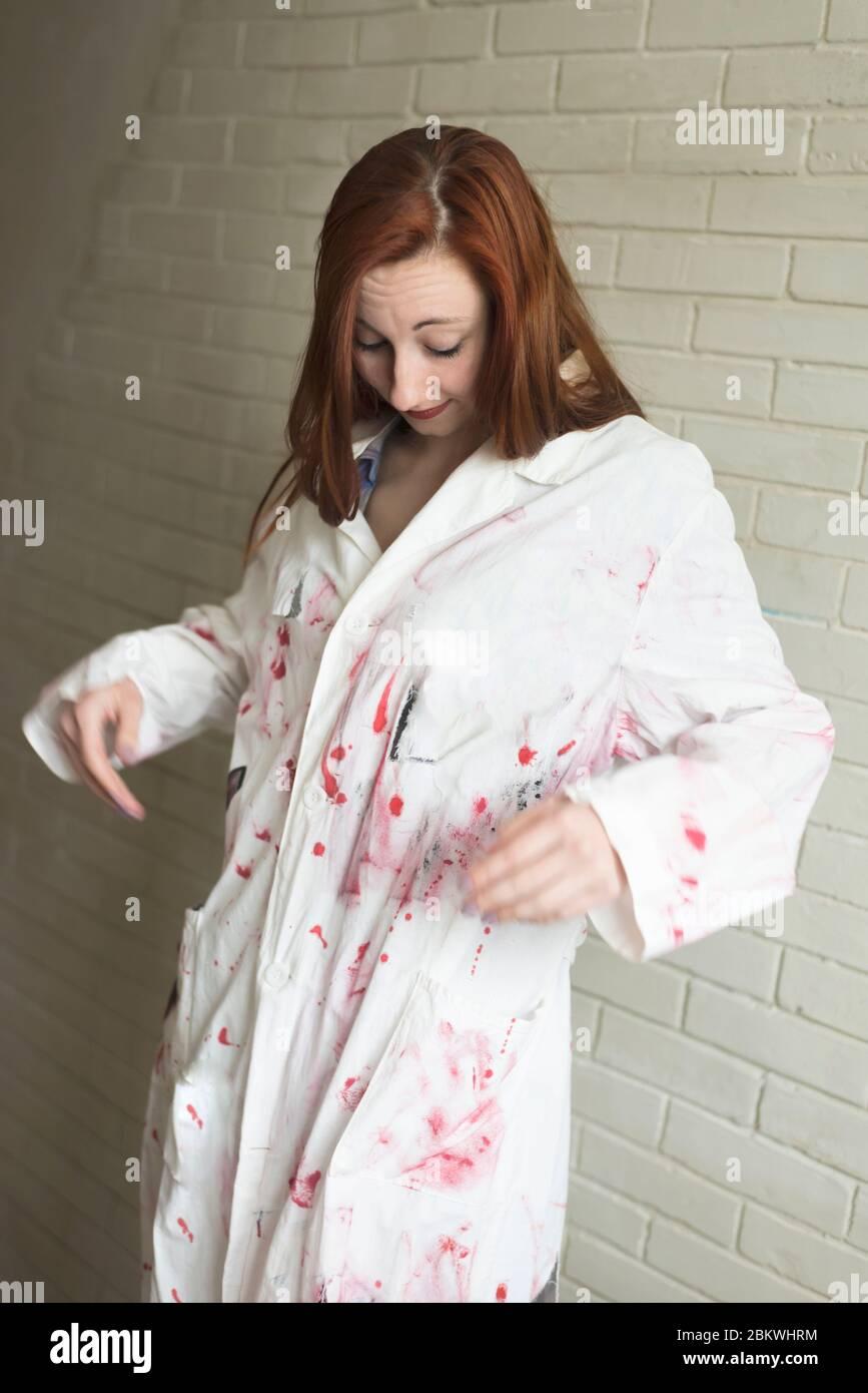 Ritratto di una ragazza dai capelli rossi in un vestito dipinto di bianco su uno sfondo muro di mattoni Foto Stock