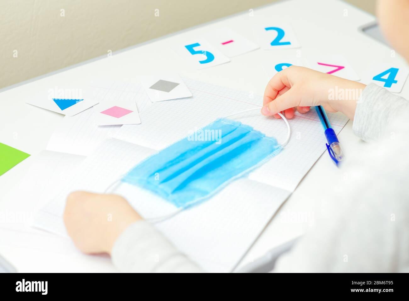 Mani per bambini che tengono una maschera protettiva medica sul notebook della scuola a casa. Concetto di apprendimento domestico. Foto Stock
