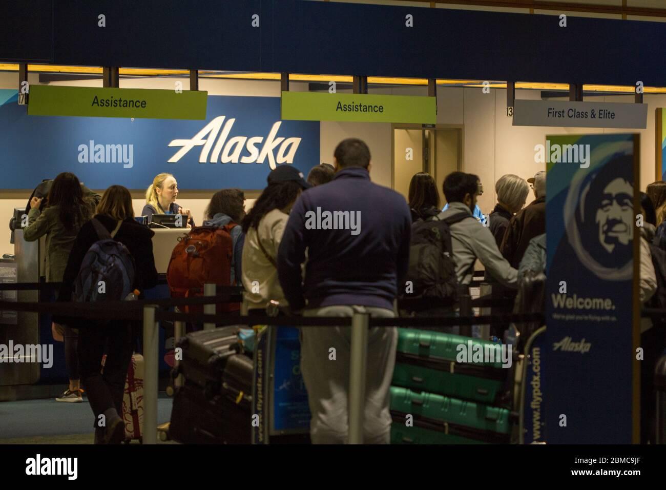 I passeggeri in attesa in fila per controllare i bagagli al banco di check-in Alaska Airlines dell'aeroporto internazionale di Portland di notte il 13 febbraio 2020. Foto Stock