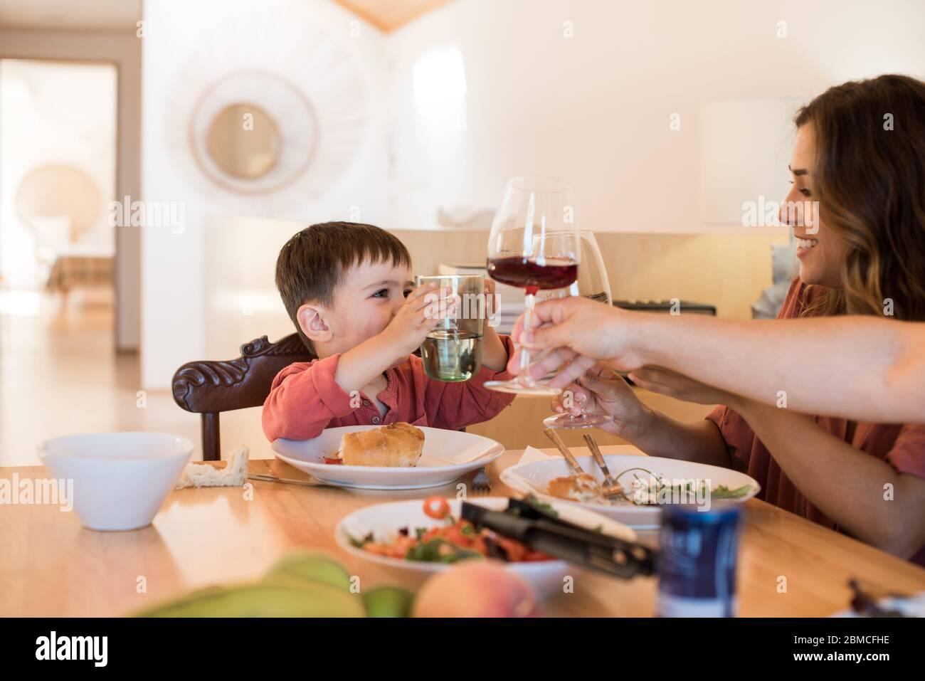 Famiglia giovane con un bambino seduto insieme per pranzo Foto Stock