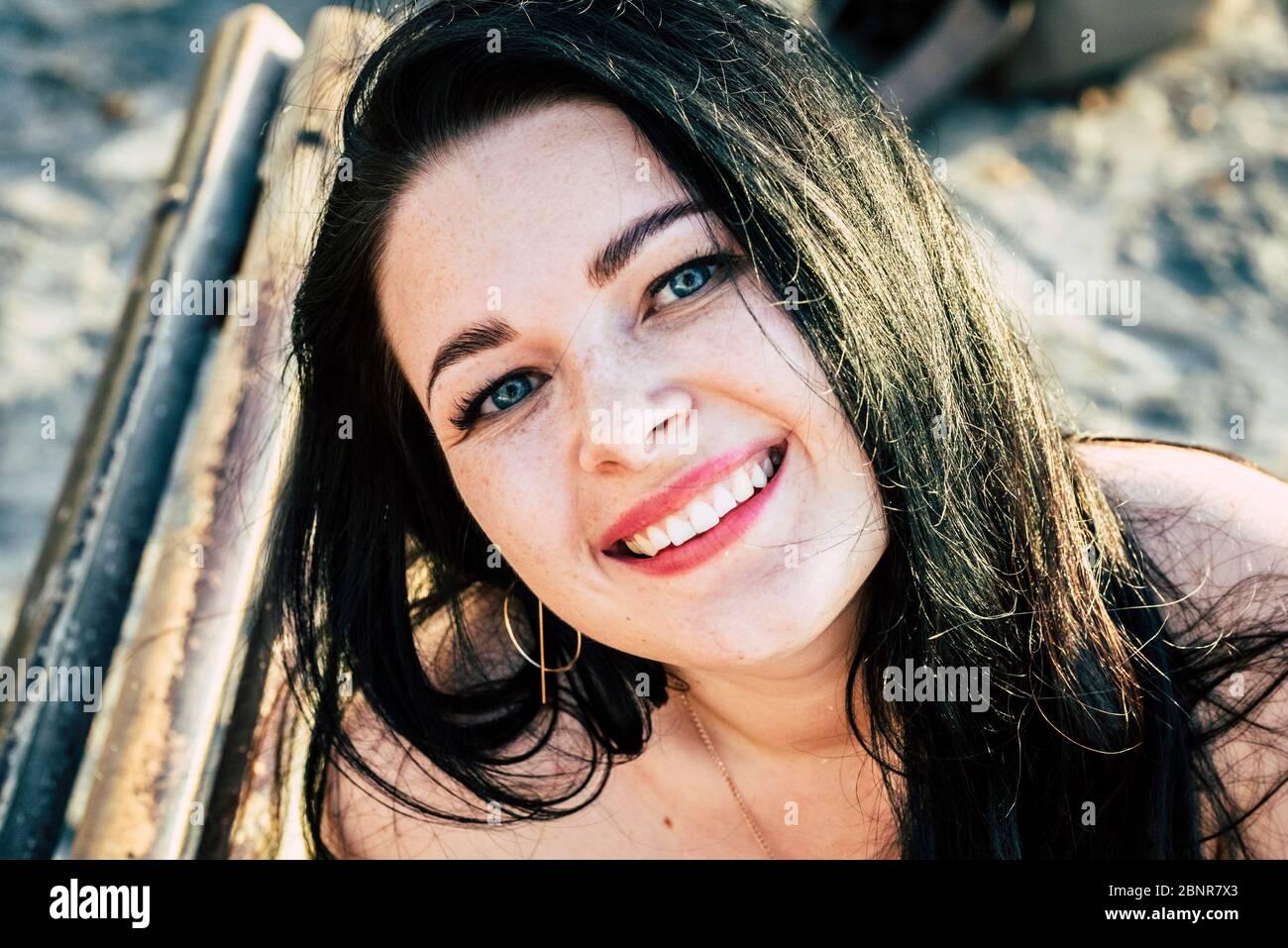 Bella giovane donna caucasica ritratto sorriso alla macchina fotografica - allegro felice gente con occhi blu e lunghi capelli neri in attività di svago all'aperto da solo Foto Stock