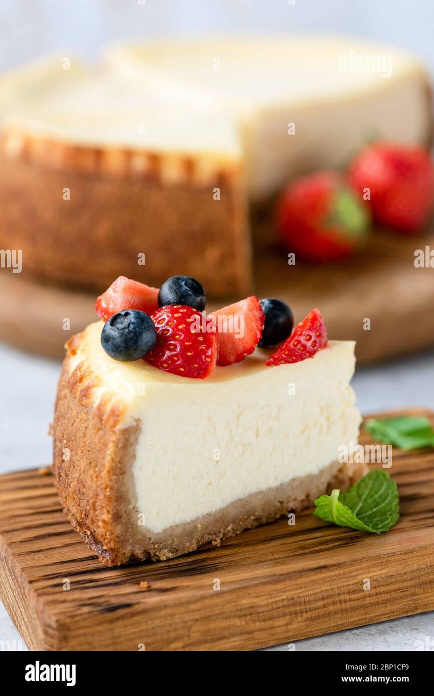 Fetta di cheesecake con frutti di bosco estivi su tavola di legno. Gustosa cheesecake Foto Stock