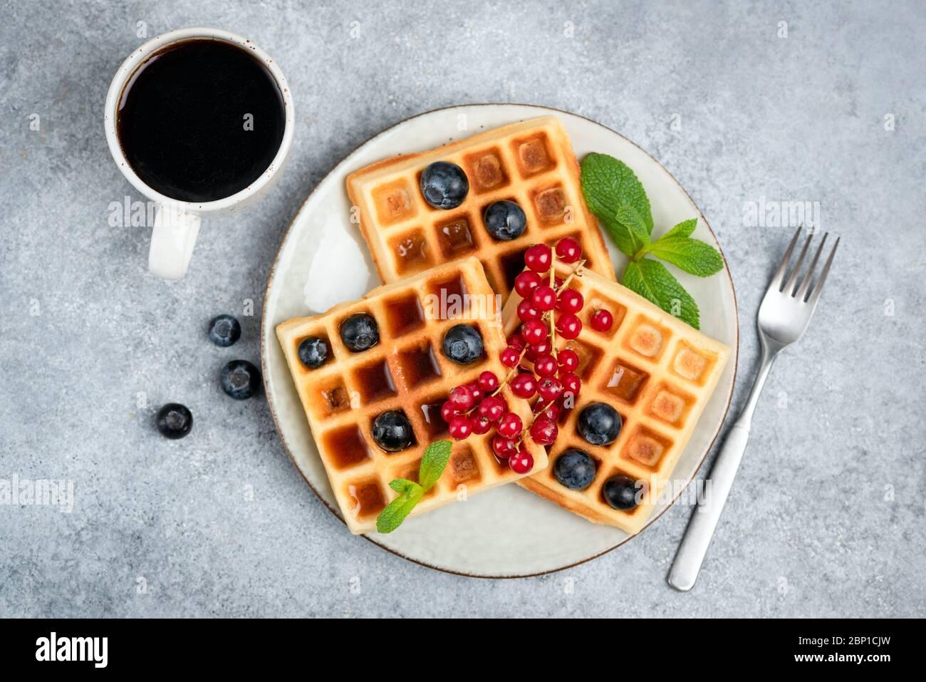 Waffle con frutti di bosco e tazza di caffè. Deliziosi waffle belgi con frutti di bosco, sciroppo e tavolino da caffè nero, vista dall'alto Foto Stock