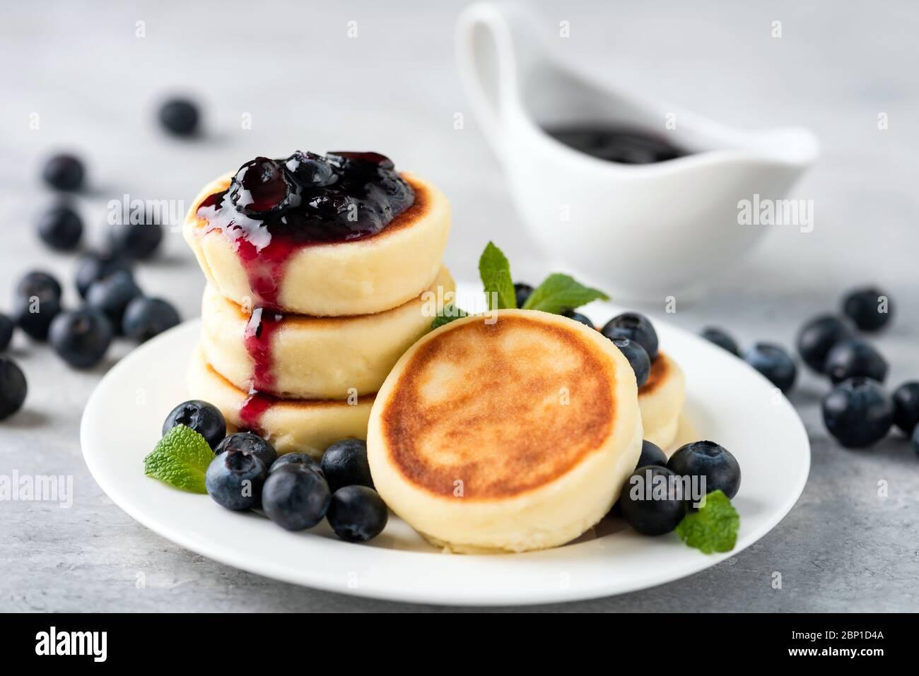 Frittelle di Syrniki o formaggio di cottage con marmellata di mirtilli su piatto bianco. Tradizionale russo e ucraino per colazione o pranzo, frittelle dolci al formaggio Foto Stock