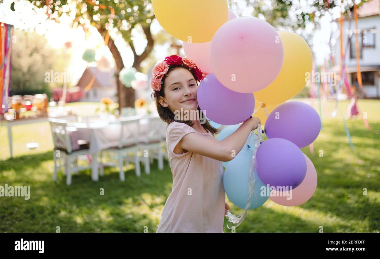 Piccola ragazza all'aperto in giardino in estate, giocando con palloncini. Foto Stock