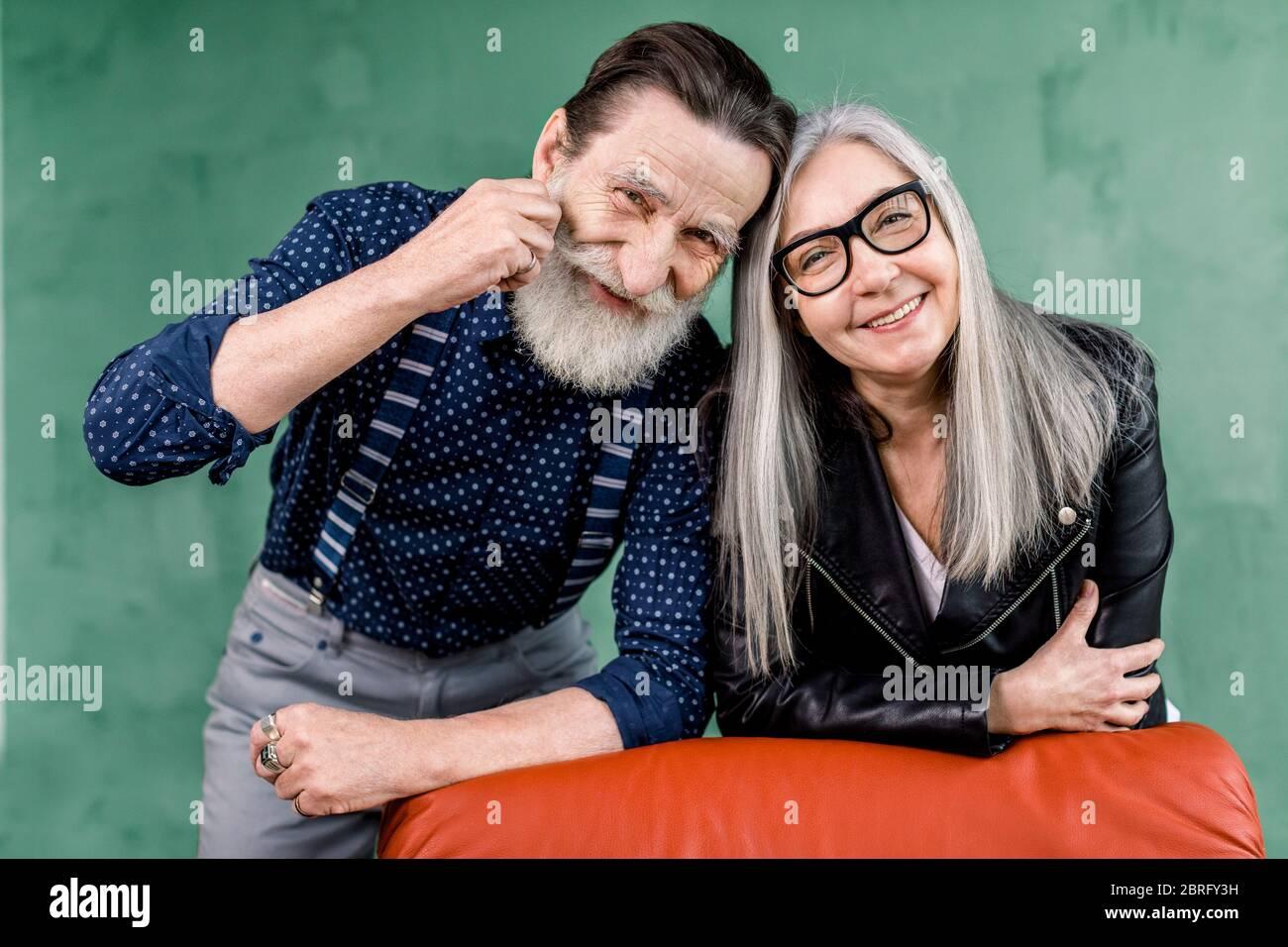 Coppia anziana. Allegra bella coppia anziana sorridente mentre è di grande umore, appoggiata su una sedia rossa morbida e toccando le fronte. Ritratto di romantico Foto Stock