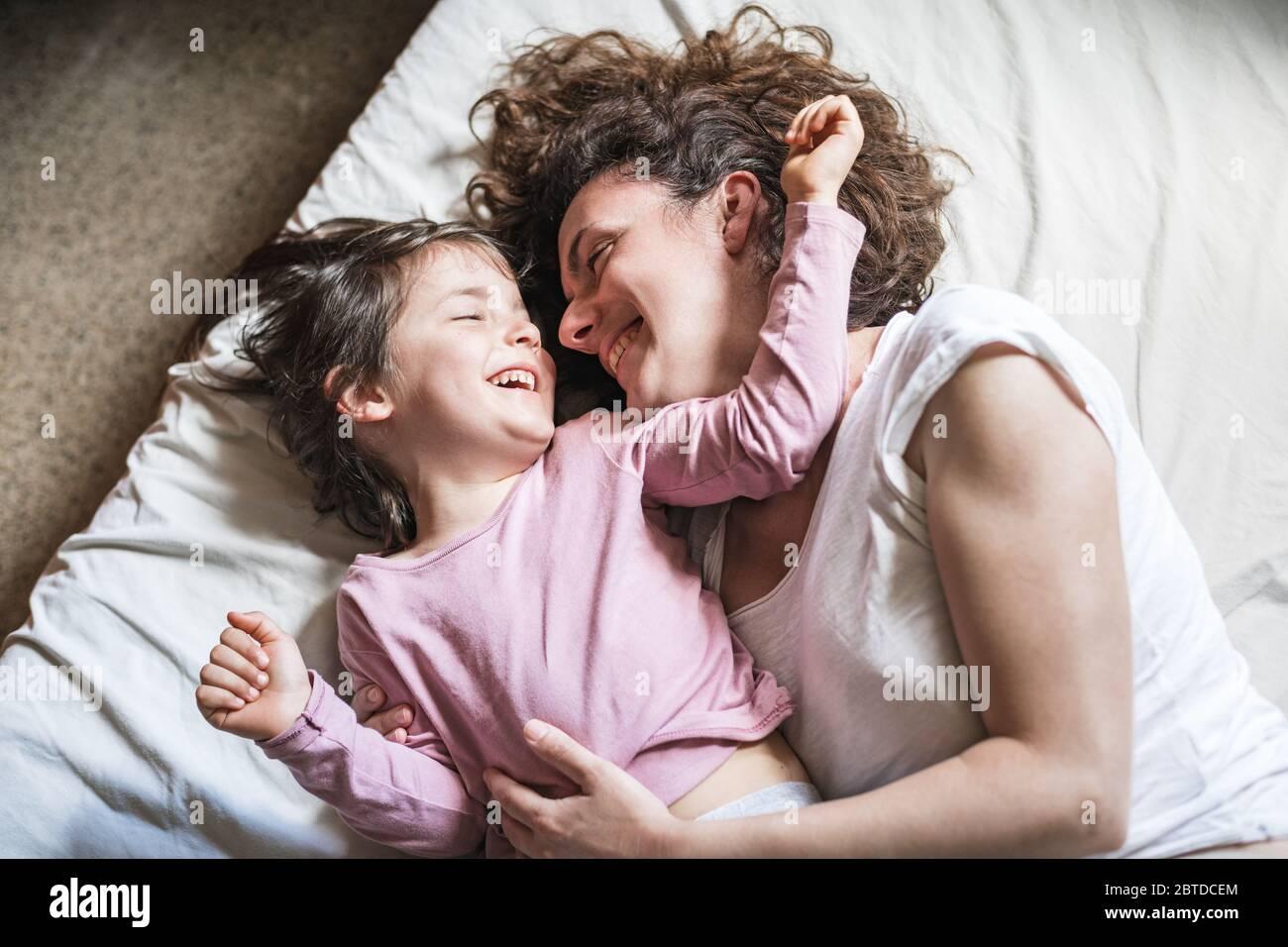 Una madre e sua figlia sorridono mentre si carezzano e giocano intorno su un letto Foto Stock