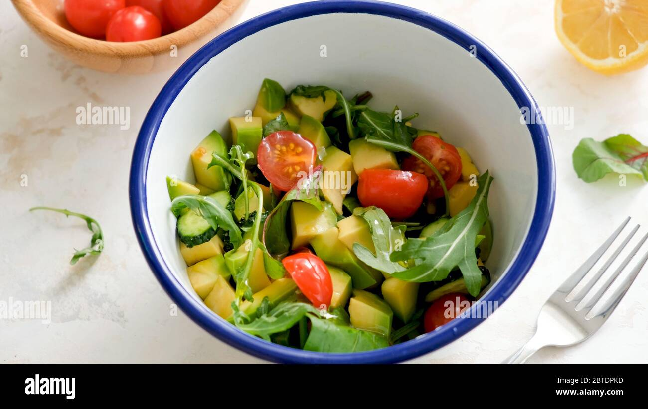 Insalata con avocado, pomodoro, rucola, cetriolo e olio d'oliva in ciotola Foto Stock