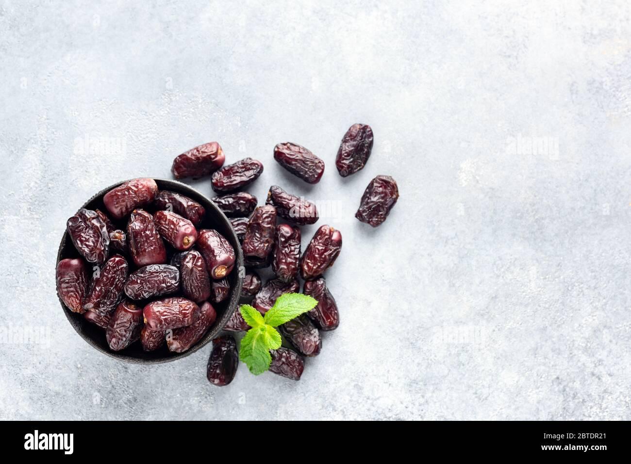 Datteri rossi secchi su cemento sfondo, tavolo Vista in alto Vegano sano frutta secca. Copia spazio per testo Foto Stock
