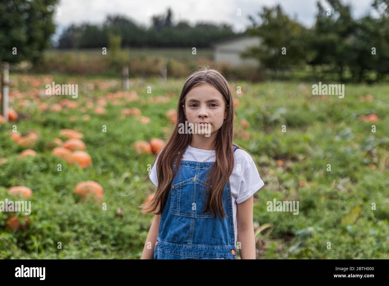 Cute ritratto della bambina in un tegolo di zucca con sfondo sfocato. Foto Stock