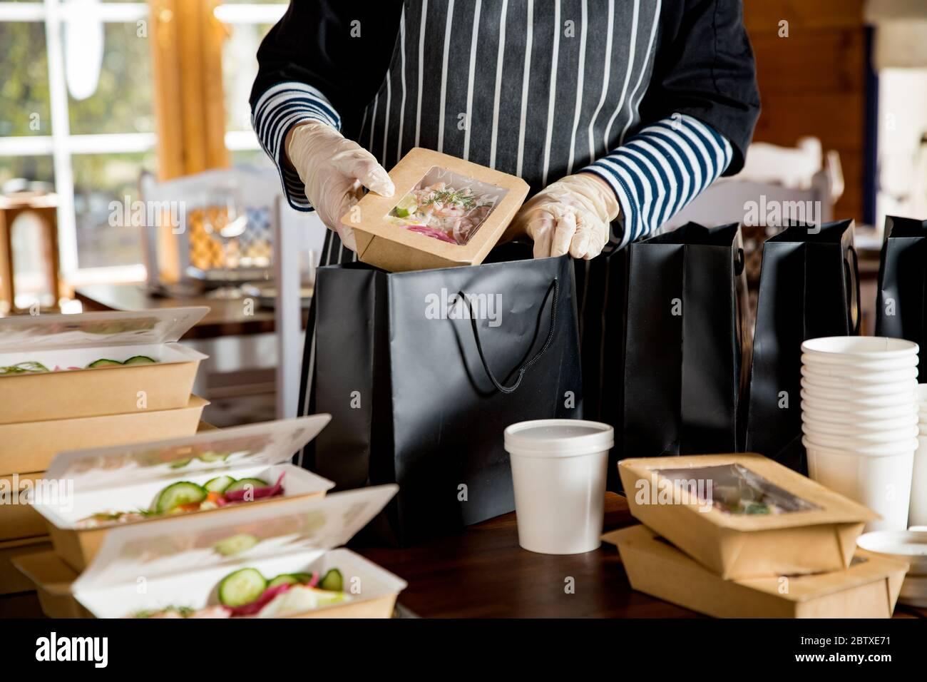 Operaio del ristorante che indossa maschera protettiva e guanti che imballano il cibo in scatola take away. Servizi di consegna di cibo e shopping di cibo senza contatto in linea. Foto Stock
