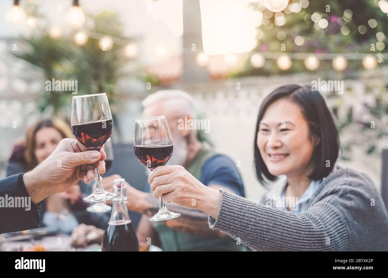 Buona famiglia mangiare e bere vino rosso a cena barbecue party all'aperto - mature e giovani cena insieme sulla terrazza Foto Stock