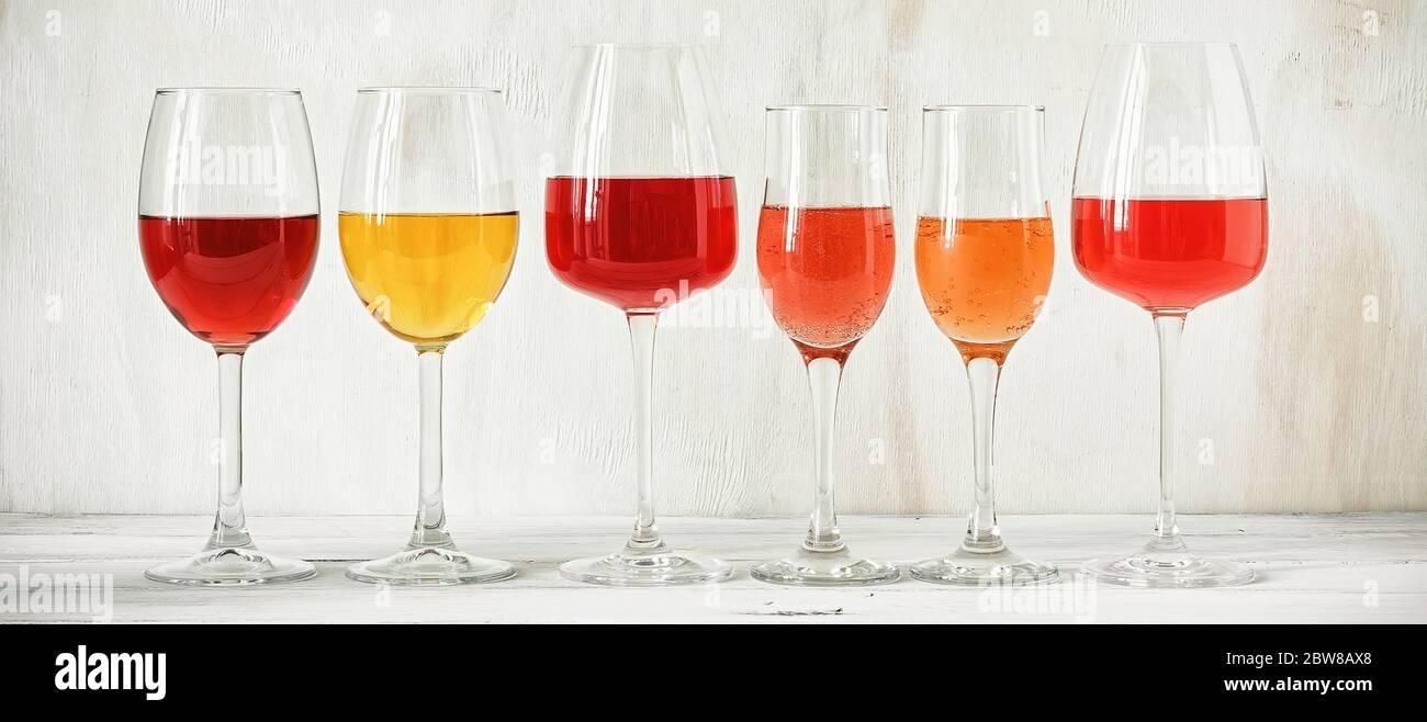 Raccolta di vari vini in un bicchiere, rosa, rosso, bianco e champagne su un tavolo rustico in legno bianco, banner. Set di vini in fila su un'annata Foto Stock