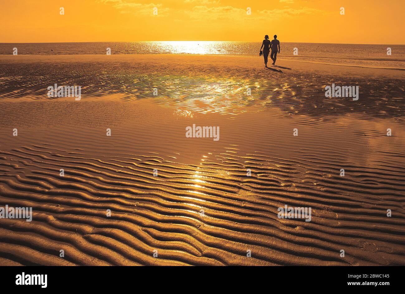 Paar wandert bei Ebbe am Strand, Sonnenuntergang, MR: SÌ Foto Stock