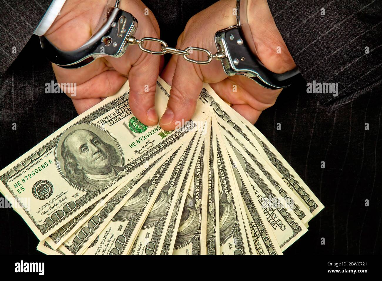 Manager mit Dollar Geldscheinen in der Hand, Hanschellen, verhaftet, Schwarzgeld, Foto Stock