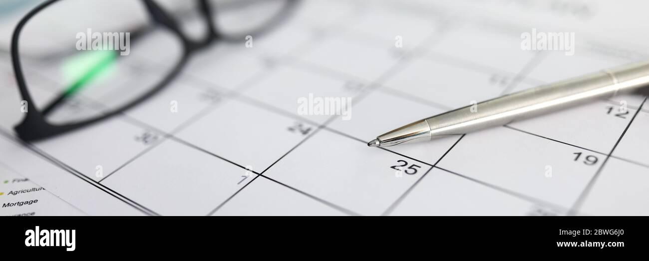 Penna in argento che giace a orari di carta bianca Foto Stock