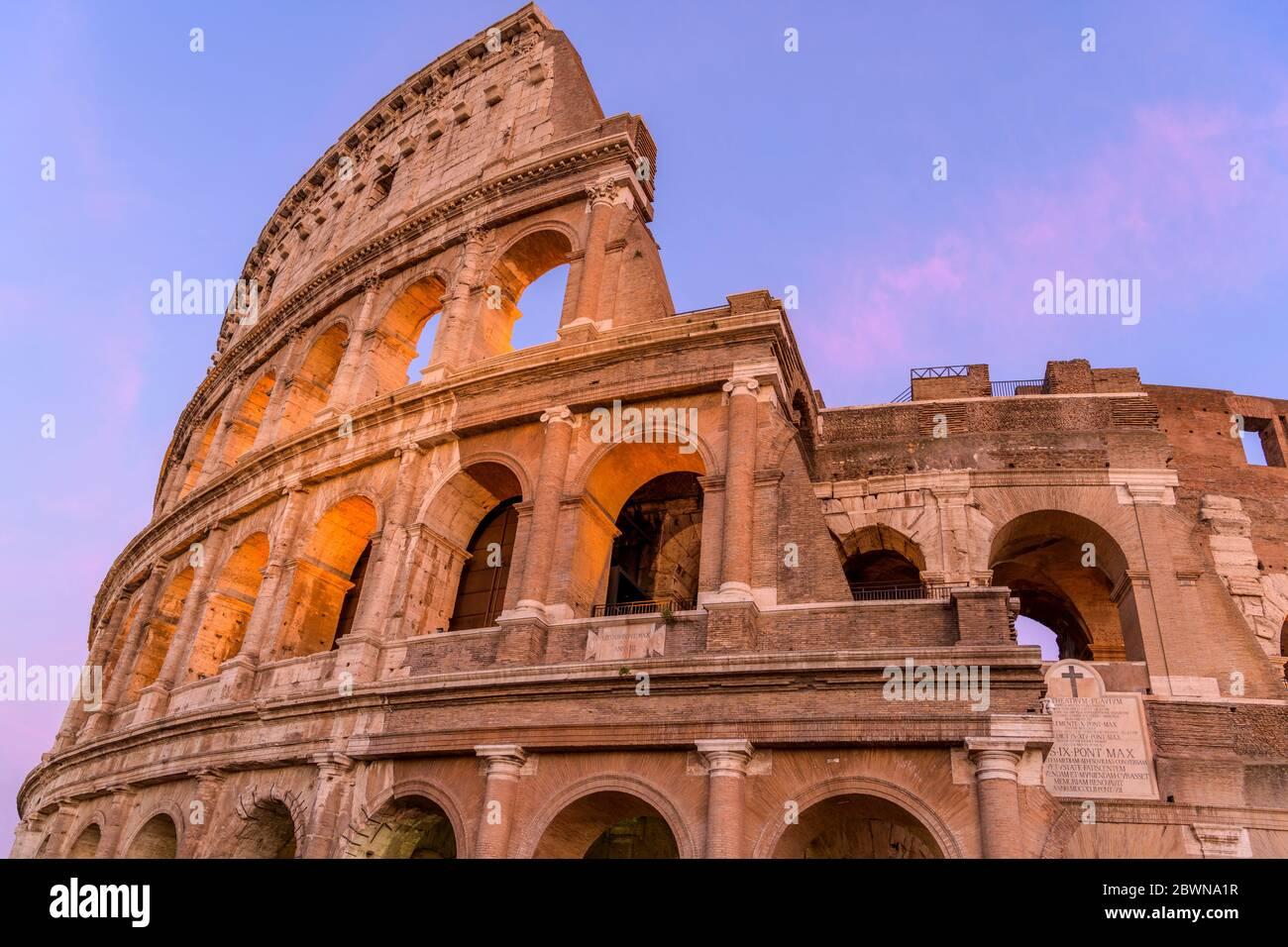 Tramonto Colosseo - Vista ravvicinata del tramonto sulla parte superiore della parete esterna ovest del Colosseo, con due placche in marmo inscritto latino. Roma, Italia. Foto Stock