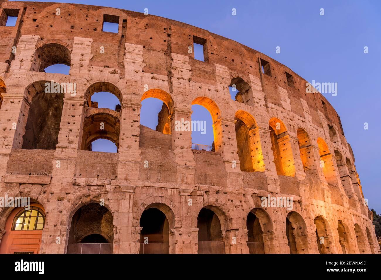 Parete esterna del Colosseo - Vista ravvicinata dal crepuscolo a basso angolo della sezione superiore della parete sud-ovest del Colosseo, contro il cielo blu chiaro. Roma, Italia. Foto Stock