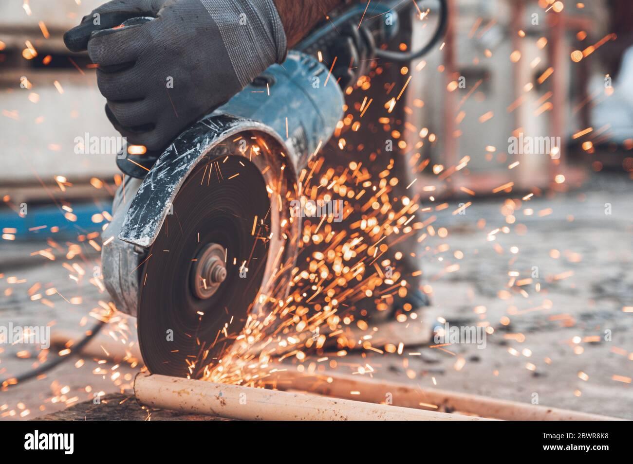 Addetto alla costruzione che utilizza una smerigliatrice angolare per tagliare il metallo nel cantiere. Foto Stock
