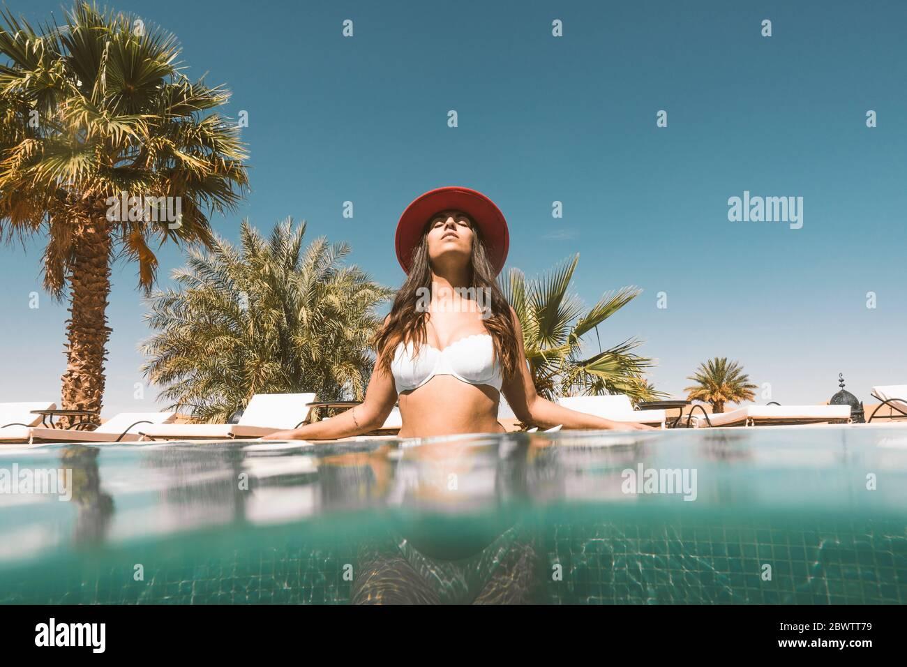Ritratto di giovane donna che si rilassa in piscina, Marocco Foto Stock
