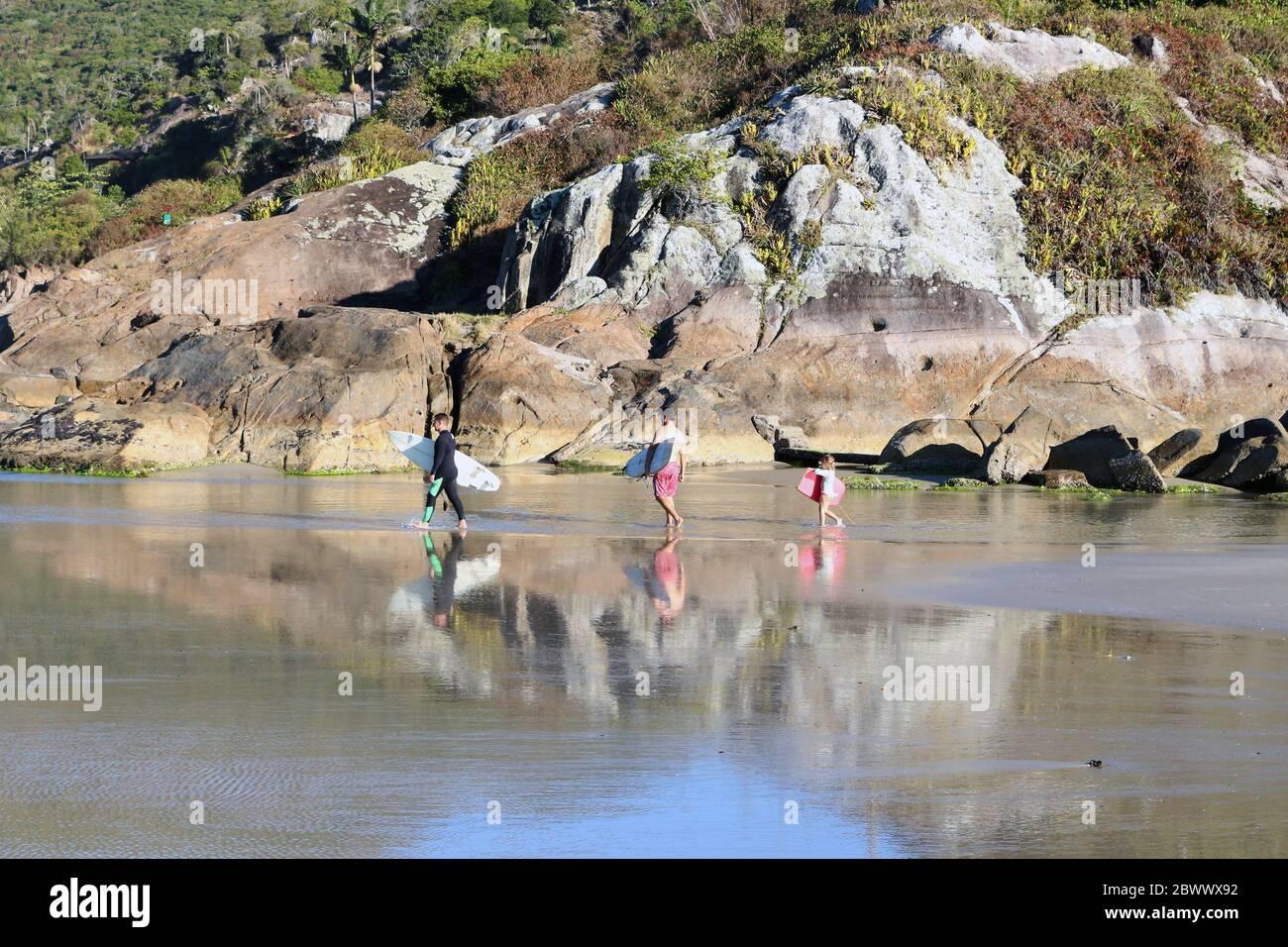 La famiglia va a surfing. Due adulti e un bambino camminano sul mare, di fronte alle rocce, con tavole. Foto Stock