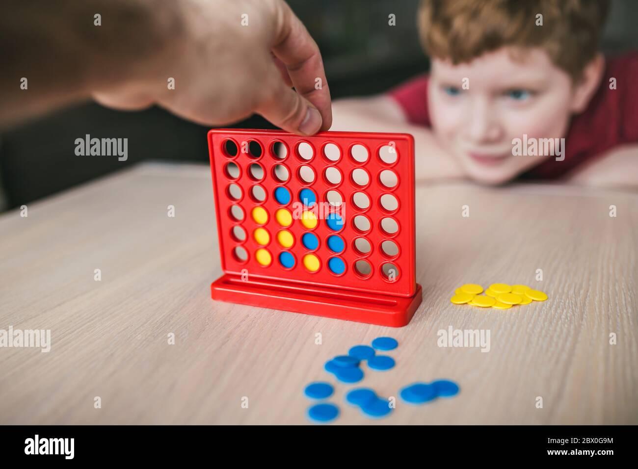 Padre e figlio giocano un gioco da tavolo di 'Collect Four in a line' - tempo libero per la famiglia Foto Stock