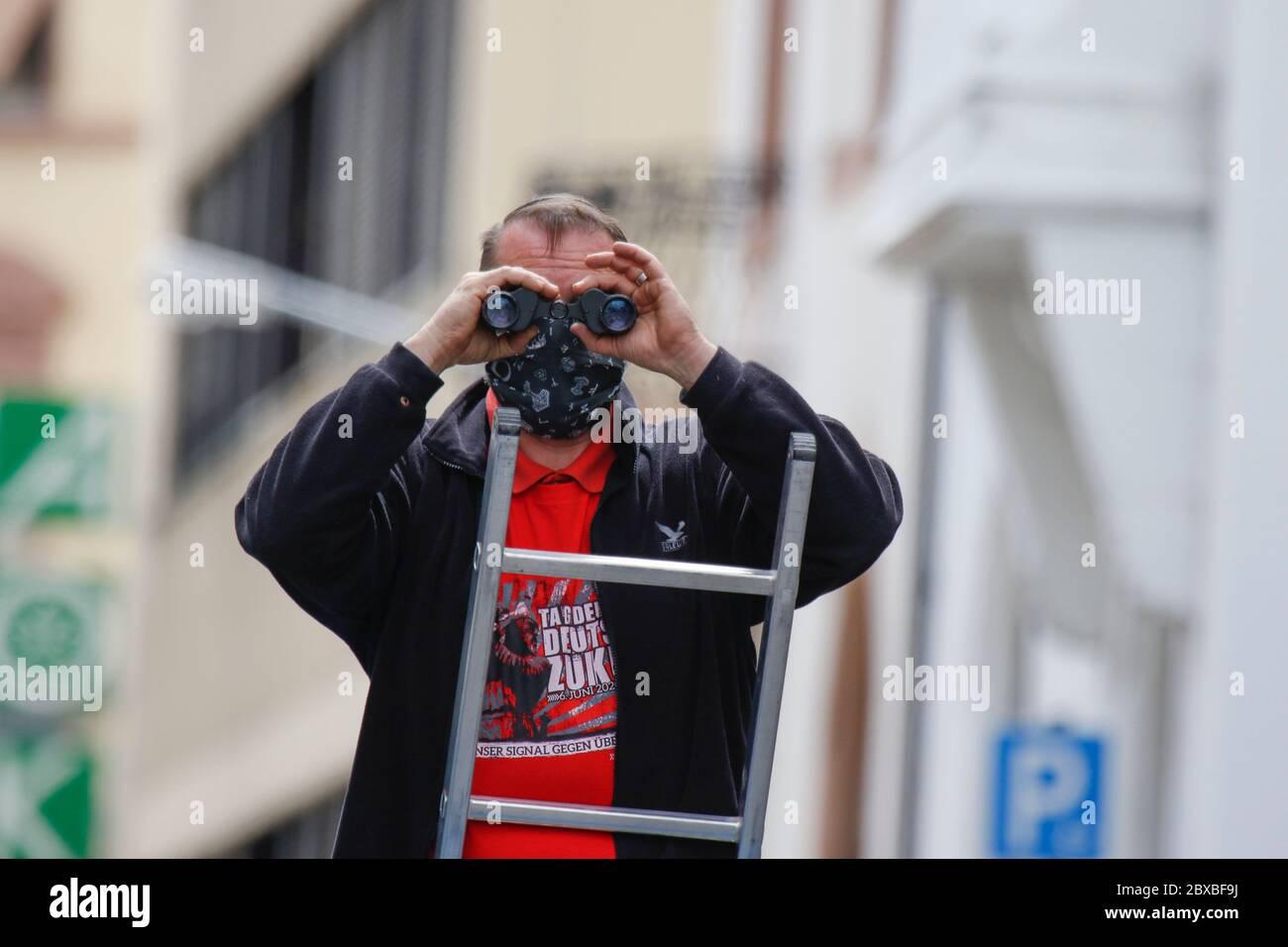 Worm, Germania. 6 giugno 2020. Un protettrice di destra si trova su una scala, guardando lungo il percorso di protesta con binocoli. Circa 50 manifestanti di destra hanno marciato attraverso il centro di Worms per il 12. E l'ultimo 'giorno del futuro tedesco'. La marcia è stata ridotta a causa di diverse centinaia di contronestori che hanno bloccato la strada della marcia di destra. la marcia è stata un evento annuale di destra in diverse città tedesche che ha attirato oltre 1000 manifestanti al suo massimo livello. Foto Stock