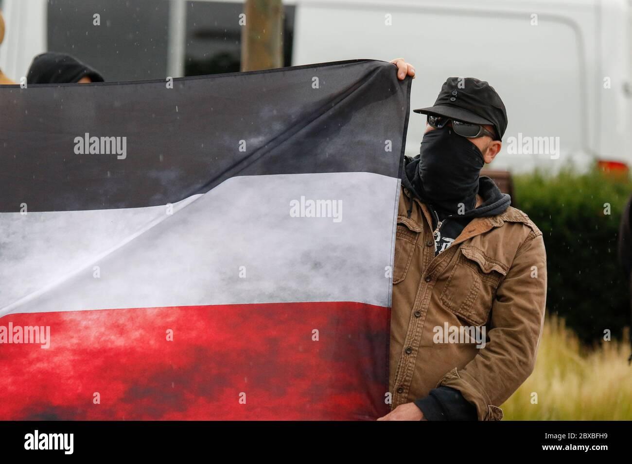 Worm, Germania. 6 giugno 2020. Un protestore porta una bandiera sporca dell'impero tedesco. Circa 50 manifestanti di destra hanno marciato attraverso il centro di Worms per il 12. E l'ultimo 'giorno del futuro tedesco'. La marcia è stata ridotta a causa di diverse centinaia di contronestori che hanno bloccato la strada della marcia di destra. la marcia è stata un evento annuale di destra in diverse città tedesche che ha attirato oltre 1000 manifestanti al suo massimo livello. Foto Stock