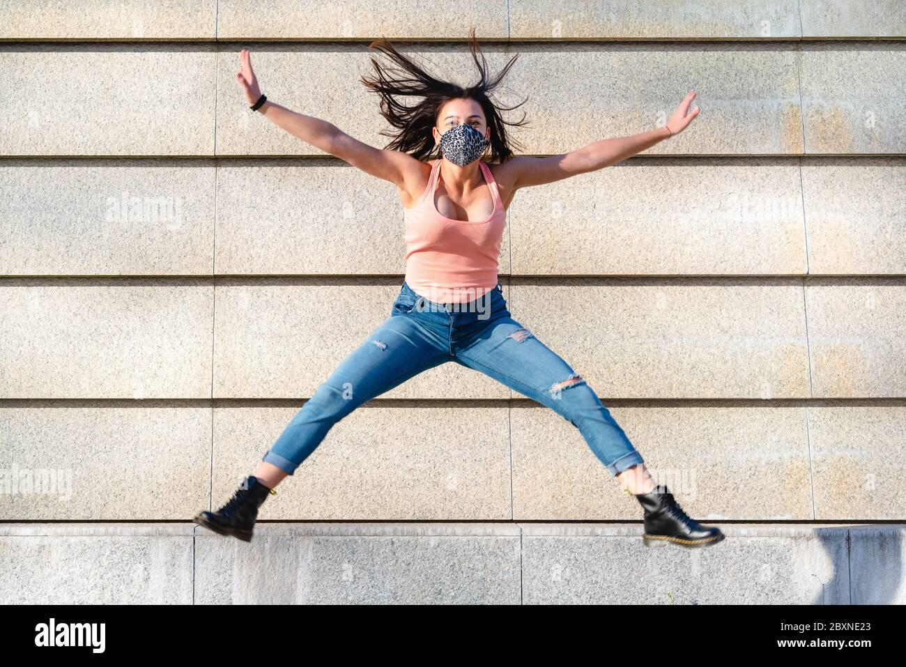 Giovane ragazza della generazione Z che indossa una maschera leopardo fa un salto acrobatico con gambe aperte, concetto di pensiero positivo e ottimismo Foto Stock