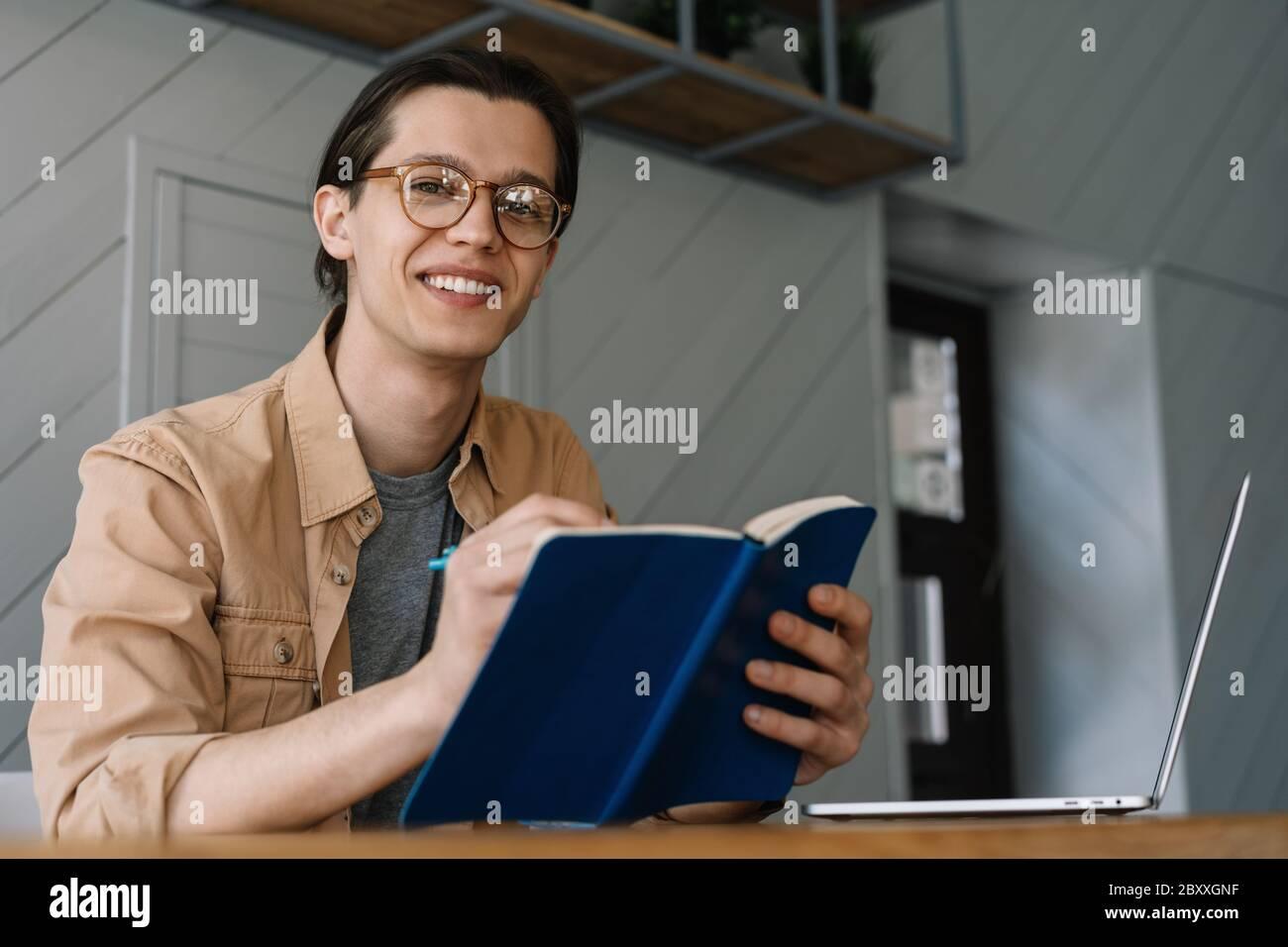 Studente che studia, a distanza. Uomo hipster sorridente prendendo appunti in notebook, lavorando progetto freelance da casa Foto Stock