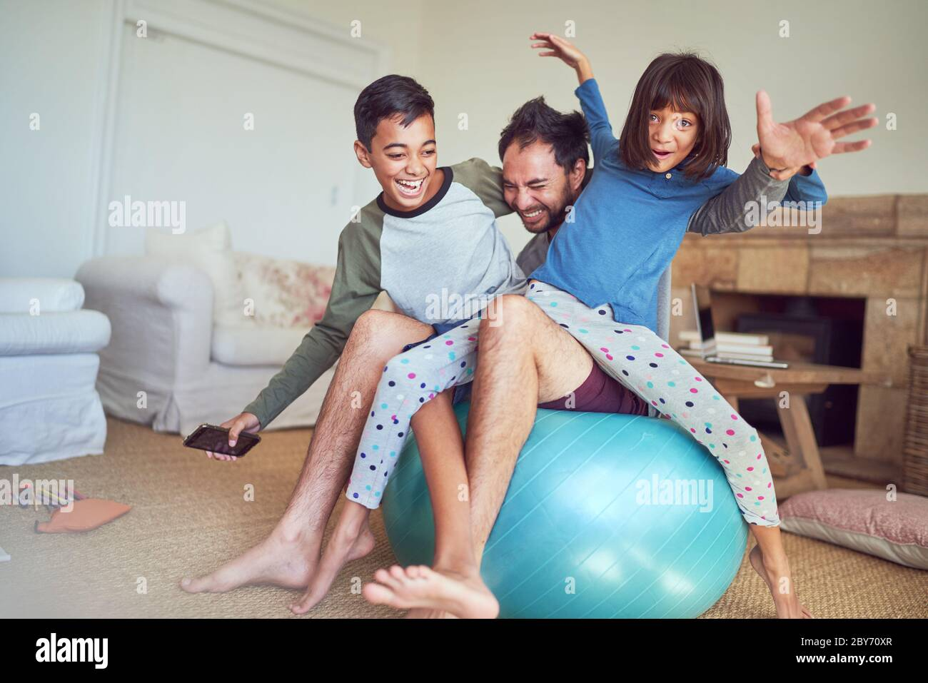 Ritratto felice famiglia che gioca sulla palla fitness in soggiorno Foto Stock