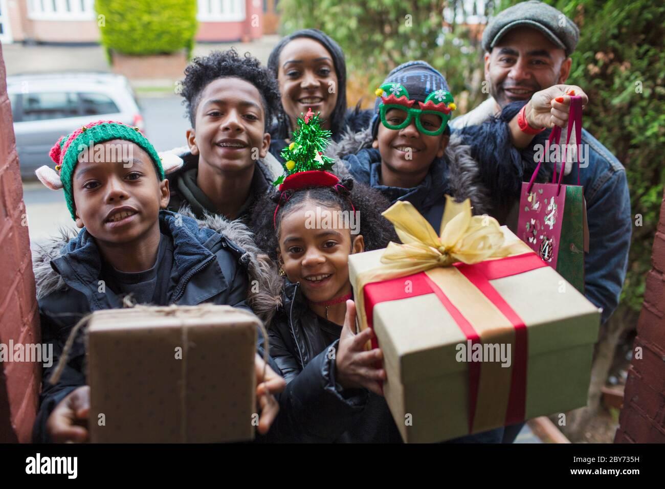 Ritratto felice famiglia arrivo con regali di Natale alla porta d'ingresso Foto Stock