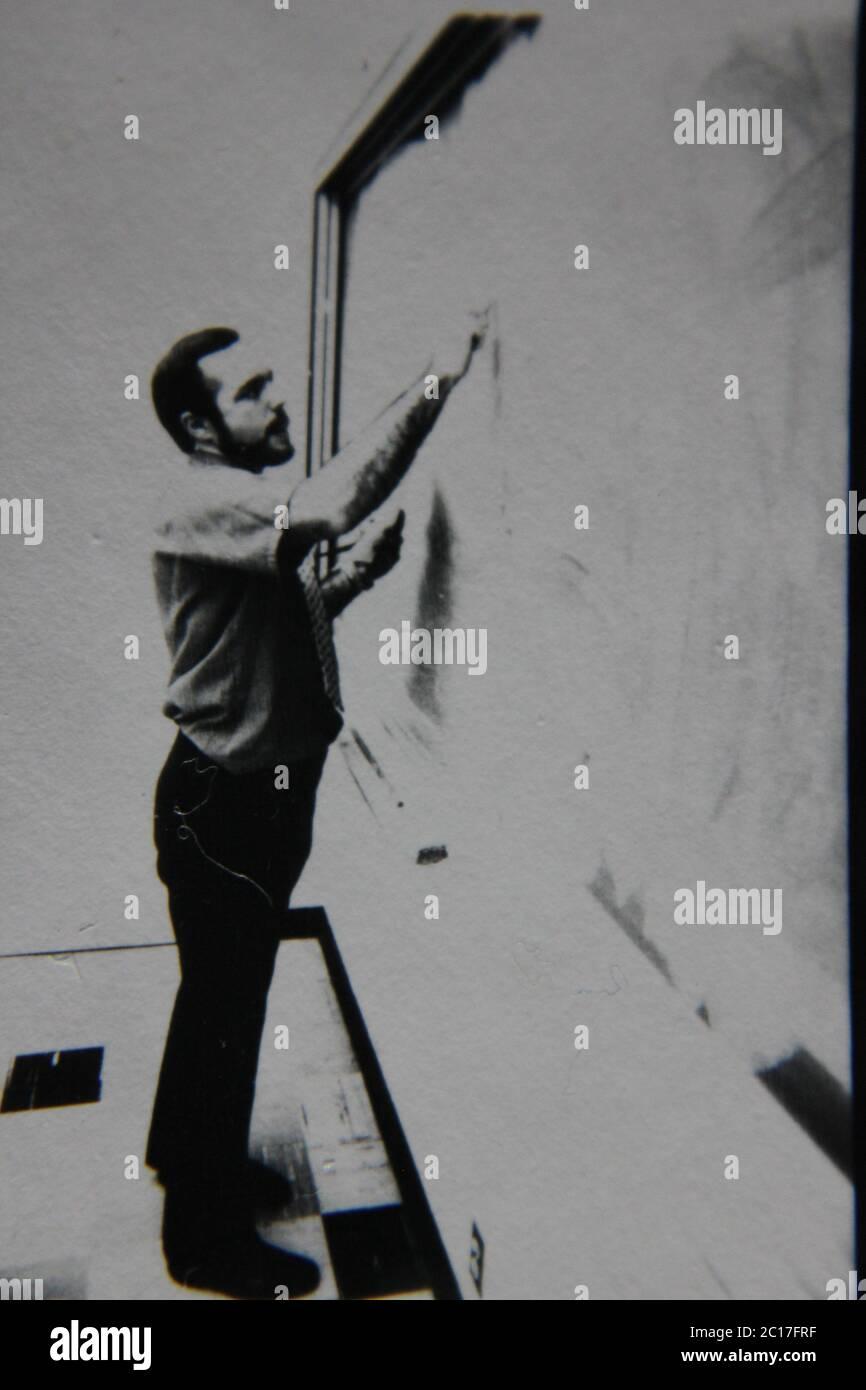 Fine anni 70 vintage in bianco e nero fotografia estrema di un insegnante in piedi alla lavagna e di scrittura su di esso. Foto Stock
