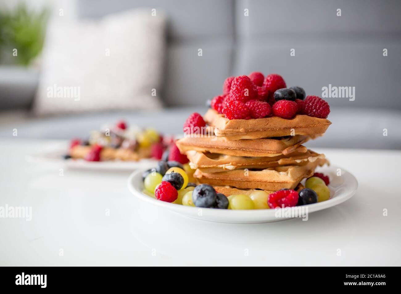 Dolce ragazzo di compleanno del bambino, mangiando waffle belgi con lamponi, mirtilli, cocnoci e cioccolato a casa Foto Stock