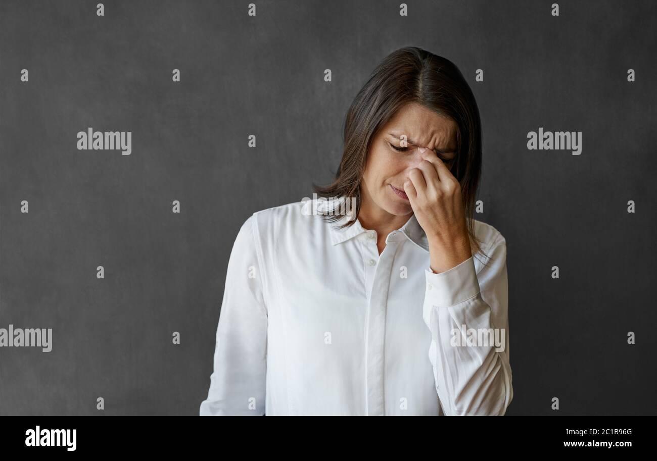 Donna d'affari che guarda stressata mentre si trova di fronte ad una lavagna Foto Stock