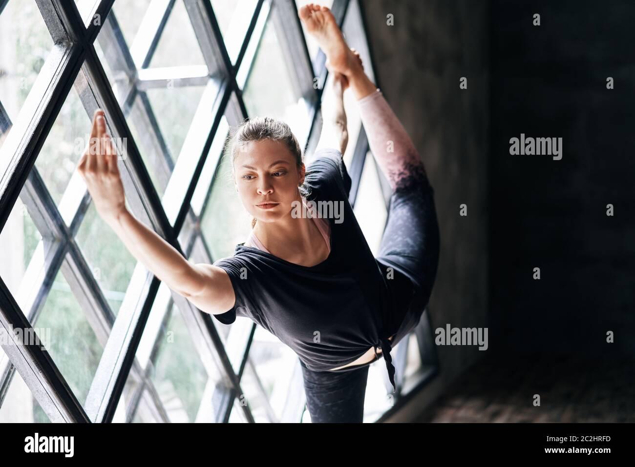 Giovane bella donna che fa yoga asana natarajasana su grande finestra triangolare sfondo Foto Stock