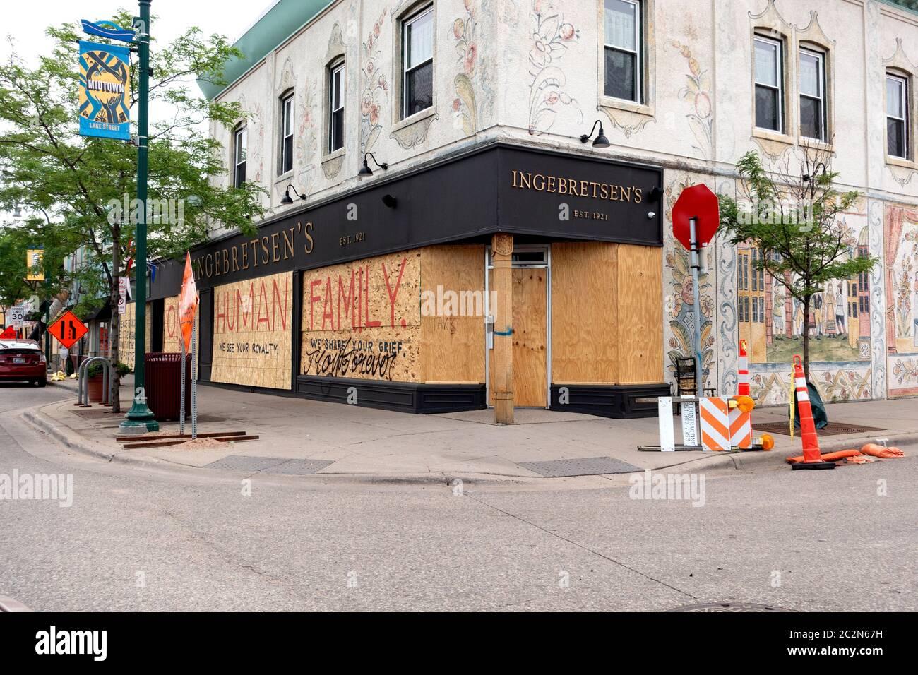 Le finestre in legno compensato del negozio di articoli da regalo e alimentari di Ingebretsen su Lake Street dichiarano 'Famiglia umana' in onore di George Floyd. Minneapolis Minnesota, Minnesota, Stati Uniti Foto Stock