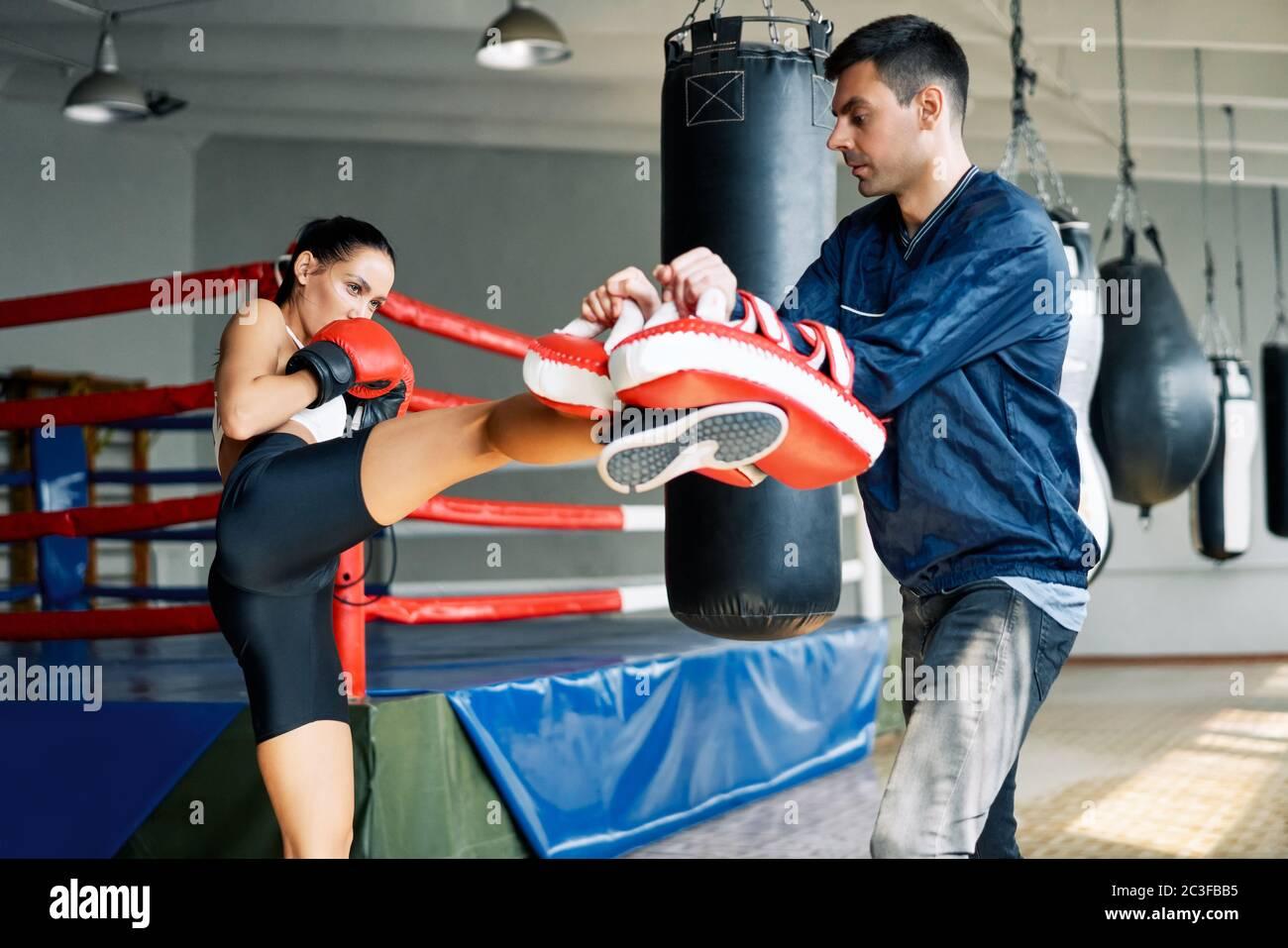 Pugile femminile kick boxing mitts tenuto da personal trainer presso palestra fitness Foto Stock