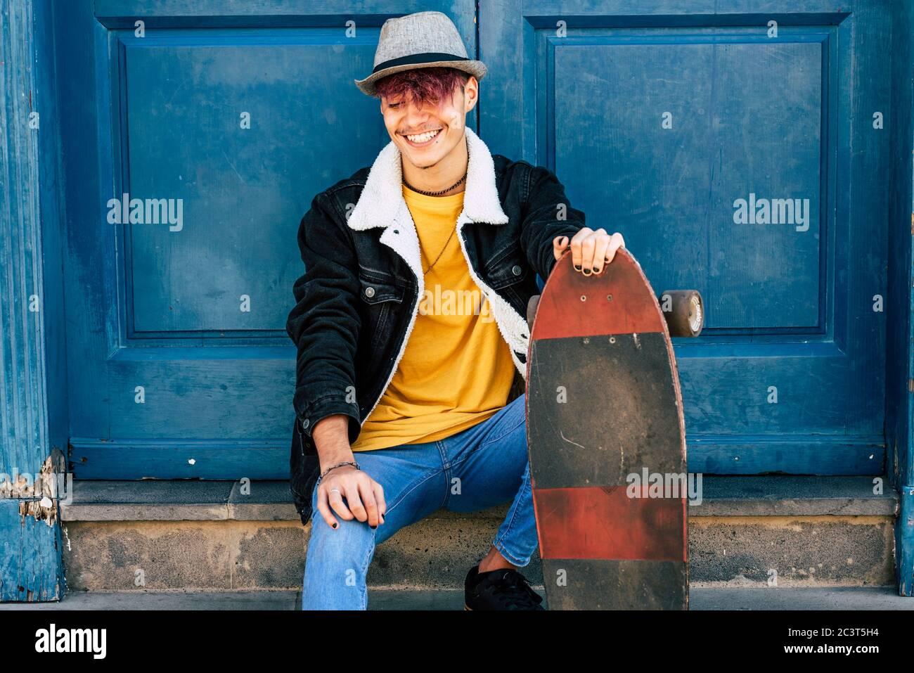 Allegro e felice adolescente sedersi fuori casa con blu vecchia porta in background - città stile di vita urbano e trendy generazione di concetto persone z - voi Foto Stock