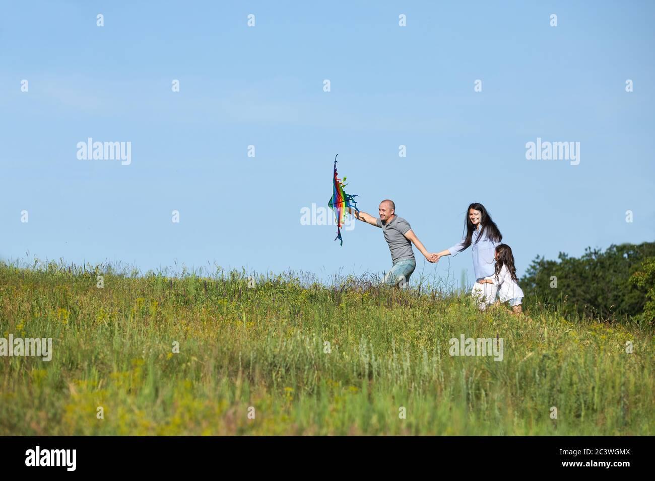famiglia felice con bambina lancia aquilone all'aperto nella natura estiva Foto Stock