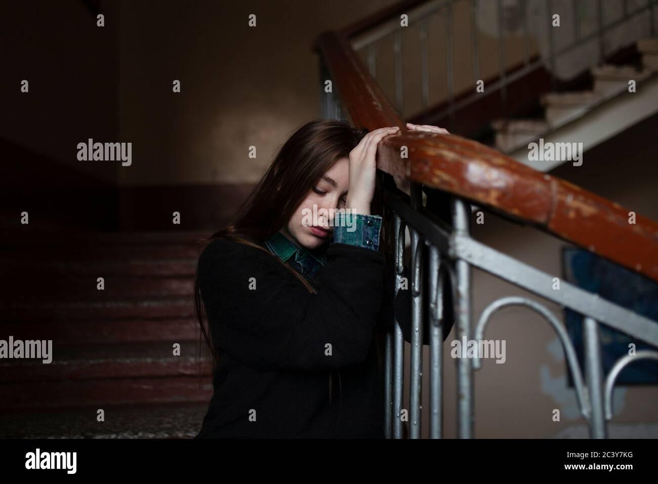 Giovane donna seduta sulle scale Foto Stock