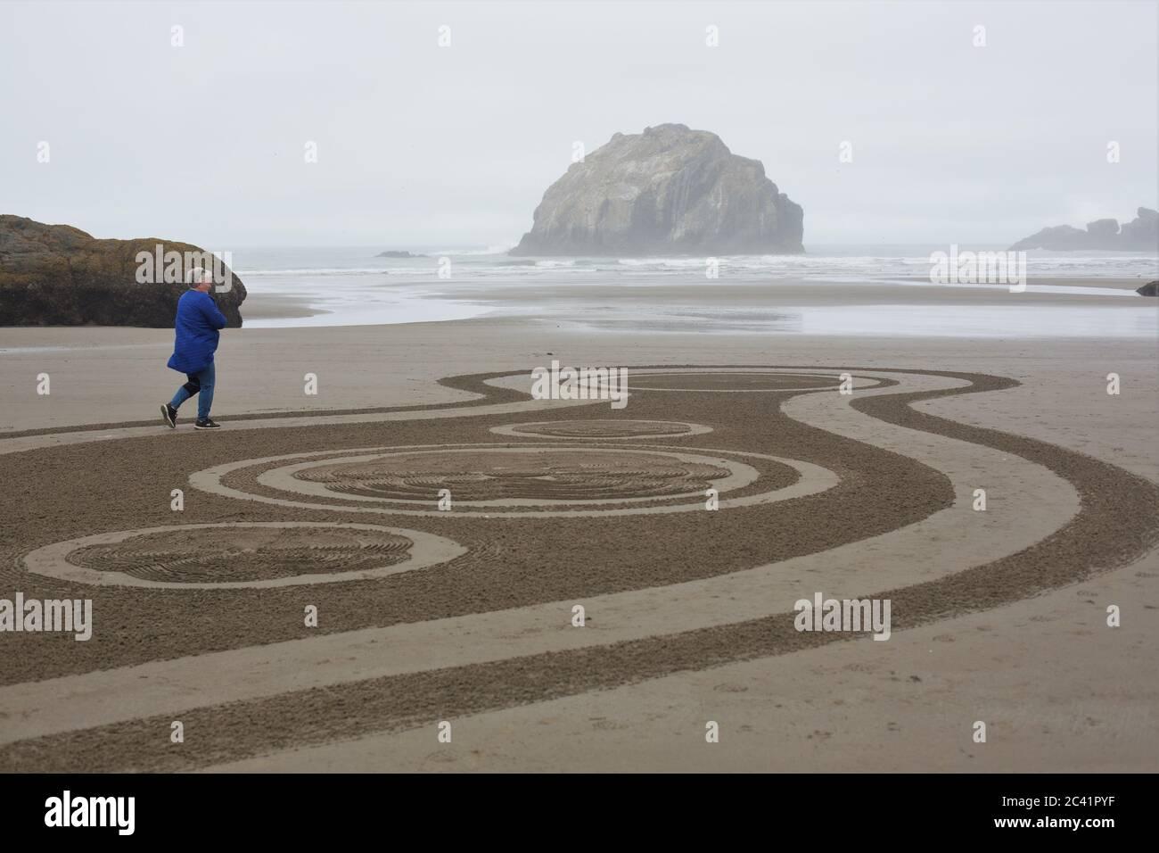 Una donna che cammina un cerchio nel labirinto di sabbia a Face Rock Beach a Bandon, Oregon, Stati Uniti. Foto Stock