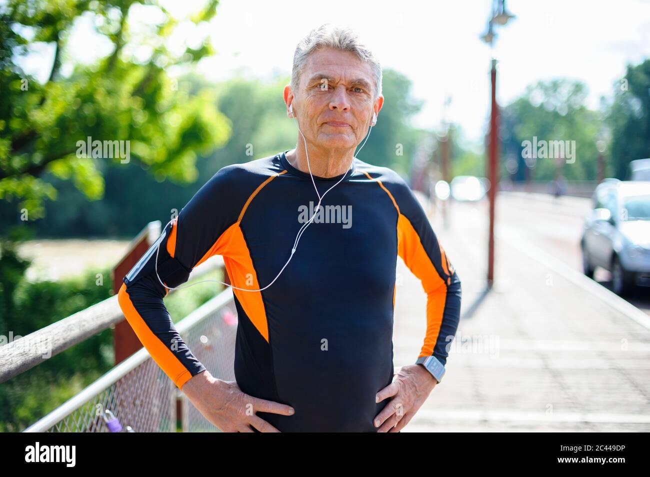 Ritratto di uomo anziano sicuro in abiti sportivi in piedi con le mani sull'anca durante la giornata di sole Foto Stock
