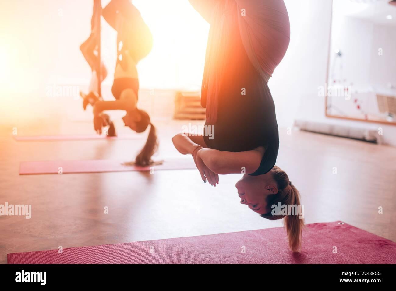 Belle ragazze giovani che fanno yoga mosca su amache, allungando la schiena e la parte inferiore della schiena, assistenza sanitaria Foto Stock