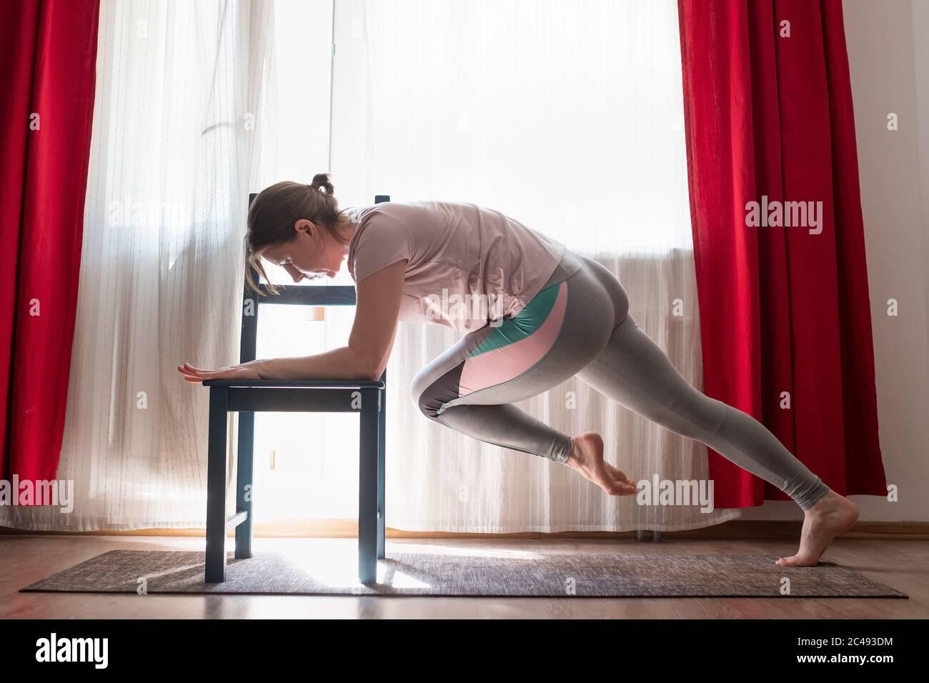 Donna che fa esercizi di spinta in su per il petto e le braccia di addestramento muscoli a casa Foto Stock