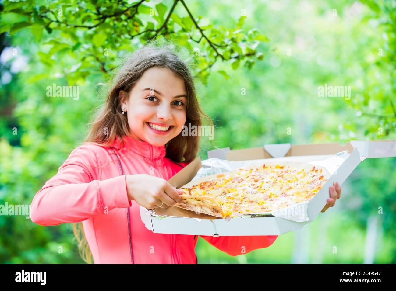Solo una fetta. Il suo cibo preferito. Il concetto di cibo spazzatura. Il bambino felice tiene la pizza grande. Consegna dei pasti in tempo. Il bambino affamato mangia la pizza. Sembra gustoso e perfetto. Senti la fame vera. Chi si preoccupa della dieta. Foto Stock