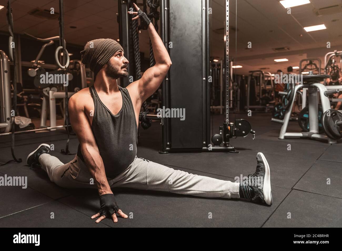 Un uomo sportivo in palestra sta facendo esercizi di yoga e arti ...